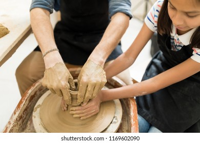 Hands of teacher and girl shaping clay on pottery wheel in studio