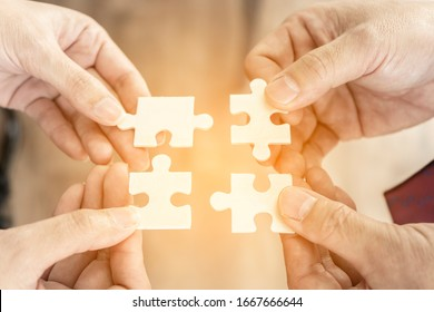 Hands of Team, agency group people connecting puzzle elements. Symbol of teamwork, cooperation, partnership. Startup employees or Finding solutions together and Goal thinking concept.