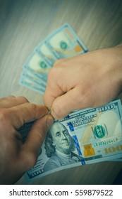 Hands tear dollar