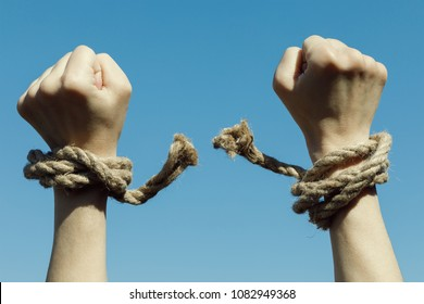Hands tearing shackles the background of blue sky. Concept of freedom