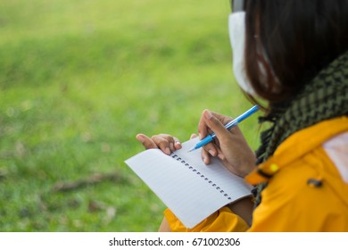 The hands of a teenage girl holding a notebook and pen on a green lawn background. When thinking about what to do, take notes and take them to the pad.