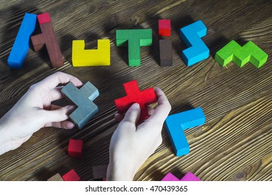 Hands that build wooden puzzles word autism. Word Autism built of wooden puzzles on a wooden background, top view. Concept of autism word, flat lay.