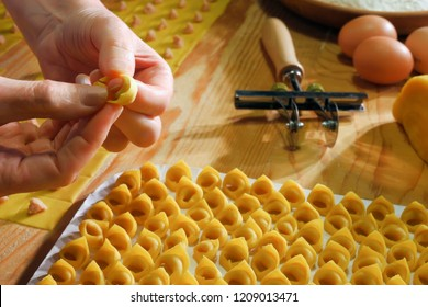 hands that fold tortellini with chopping board and tortellini in the background