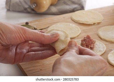 Hands that mold dumplings and wooden board with circles of dough and meat ball