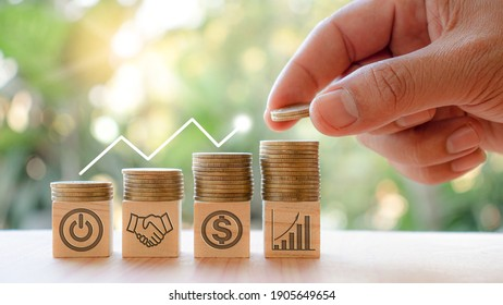 Hands that are stacking coins to save money And the symbols on the wooden blocks indicate business start and growth. For future stability