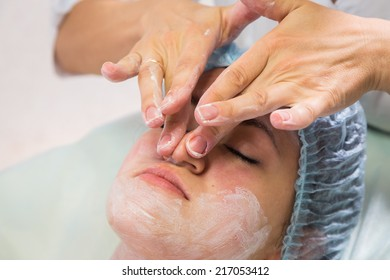 Hands of therapist apply cream to face of woman. Concept of care and youth.Girl with a beautician at spa salon.Cosmetology, facial, beauty. Article about cosmetology.
