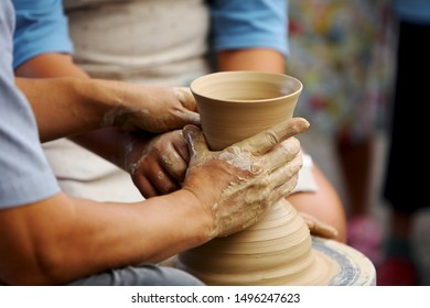 the hands of those who are learning pottery