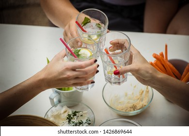 Hands of three women viewed from above seen cheering or toasting with glasses of gin tonic drink. Other healthy foods are seen around, like dips and carrots