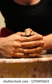 Hands throwing a pot on a potter's wheel.