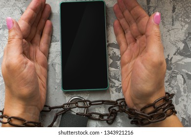 hands tied with a chain, smartphone. the concept of disability, prohibition.
