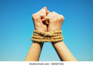 Hands tied up with rope against blue sky