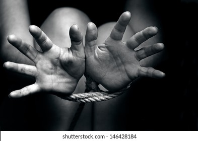 Hands tied up with rope of a missing kidnapped, abused, hostage, victim woman in pain, afraid, restricted, trapped, call for help, struggle, terrified, threaten, locked in a cage cell.