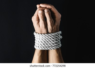 hands tied with a rope on a black background, the concept of stealing people, right day