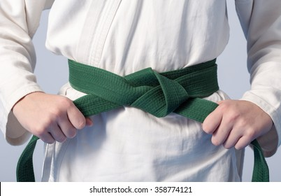 Hands tightening green belt on a teenage dressed in kimono