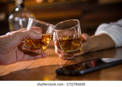 hands toasting whisky in pub