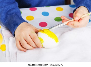 Hands of toddler boy painting colorful eggs for Easter hunt, traditional action in Germany for Eastern holiday, indoors