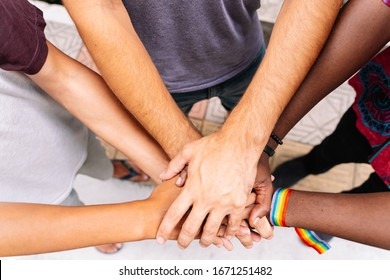 Hands together of a group of people of different ethnicities with an lgtb flag bracelet in the street