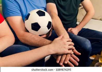 Hands together and soccer ball in the middle, family soccer fans