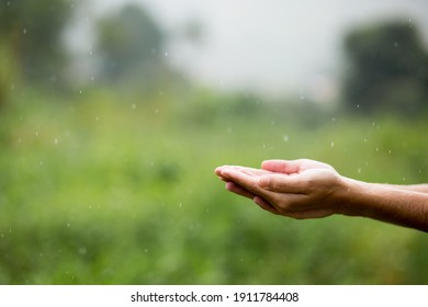 Hands together under raindrops. Washing hands in the rain.