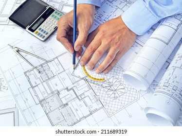 Hands with the tool on a background of project drawings