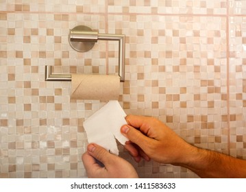 hands with torn toilet paper at the end
