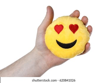 In the hands of a toy smile emoji. Isolated background