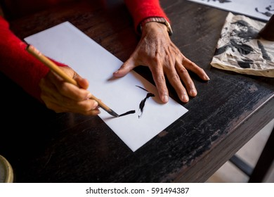Hands of traditional calligrapher in Hoi An, Vietnam