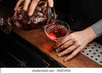 Hands transfusing a fresh alcoholic drink into the cocktail glass against the background of bottles