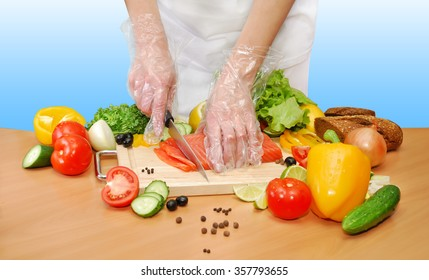 hands in transparent plastic gloves with a knife cut the fish and vegetables in the kitchen