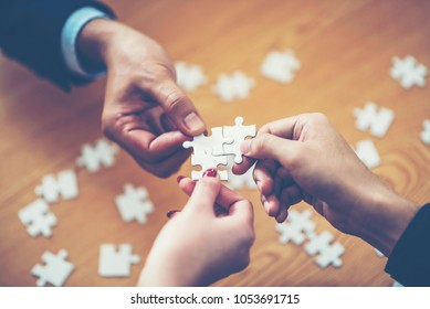 hands trying to connect couple puzzle piece with background, one part of whole. symbol of association and connection. business strategy.