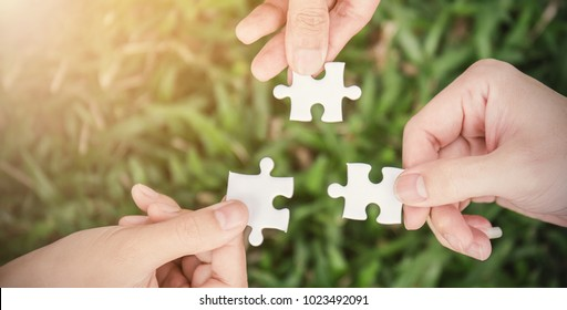 Hands trying to connect puzzle pieces with sunset green grass background. Teamwork hands holding white jigsaw symbol of association and connection. Business strategy team together concept banner.