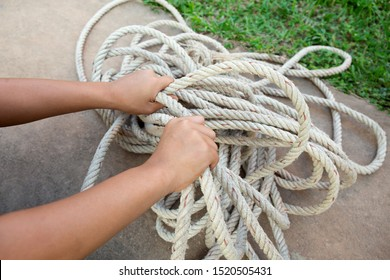 hands trying to untangle a rope