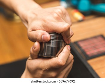 Hands twisting the cap of a steel grinder made for cannabis (marijuana) buds.