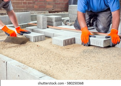 Hands of two builders laying paving stones on a prepared levelled sand base placing them into position around a new house
