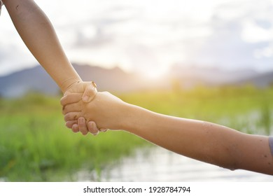 Hands of two child holding each other on nature background. concept of mutual assistance and friendship