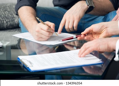 Hands of two men signed the document, sitting at the desk