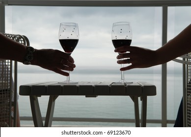 Hands of two people holding glasses of red wine on a balcony overlooking a lake.