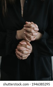 The hands of two people intertwined on a black background