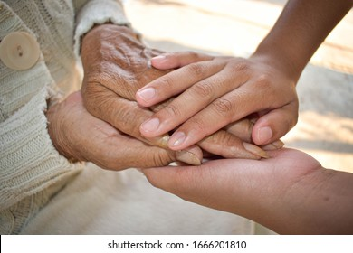 Hands of two people represent family warmth and care for the elderly.