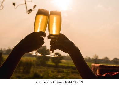 Hands of two people toast champange celebrating under afternoon sunlight, celebrating occation