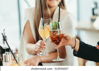 hands of two unknown women holding cocktails with mint  in restaurant