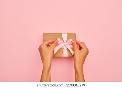 Hands tying a bow on present box on pink flatlay