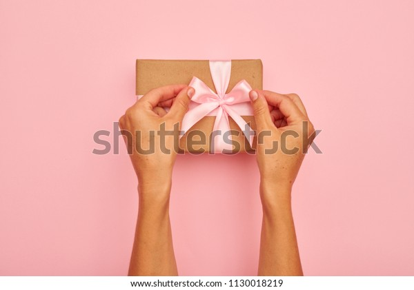 Hands tying pink bow on a present box