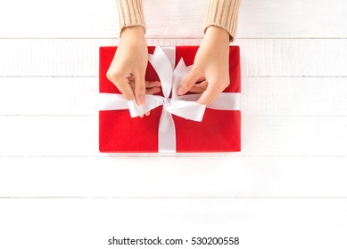Hands tying ribbon on red gift box, top view
