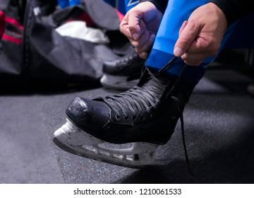 hands tying shoelaces of ice hockey skates in locker room