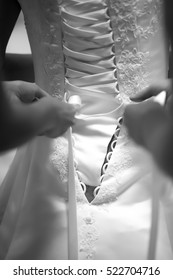 hands tying a wedding dress