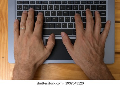 hands typing on a computer top view