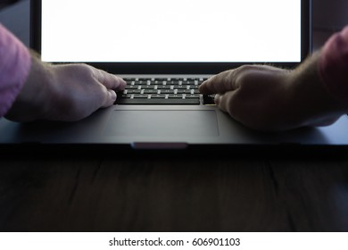 Hands typing on laptop computer on wooden table.