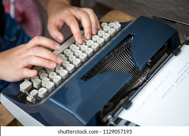 Hands typing on a mechanical qwerty keyboard of an old fashion typewriter