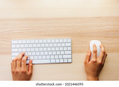 Hands typing on wireless keyboard on wooden desk with copy space